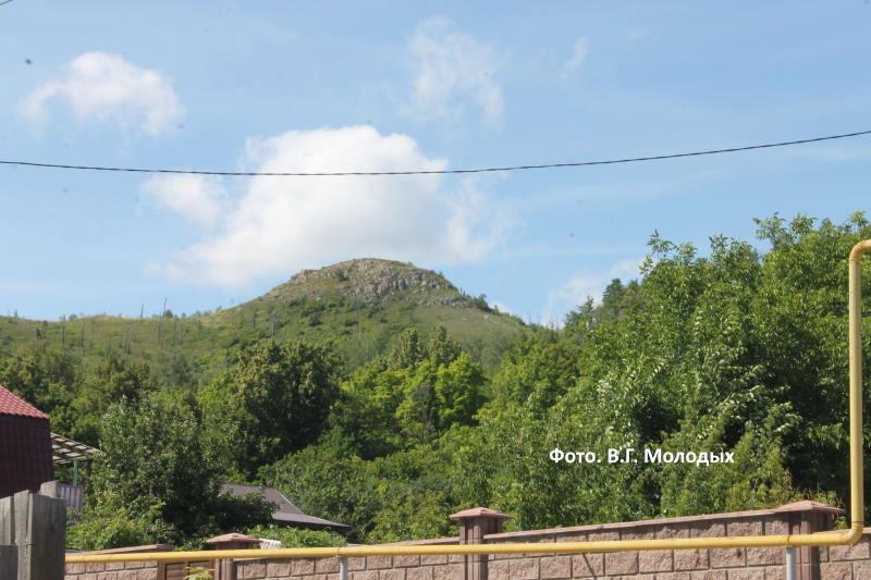 Через забор видна гора Шишка